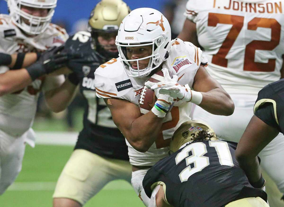 Roschon Johnson battles for yards in the middle for the Longhorns asTexas plays Colorado in the Alamo Bowl at the Alamodome on Dec. 29, 2020.