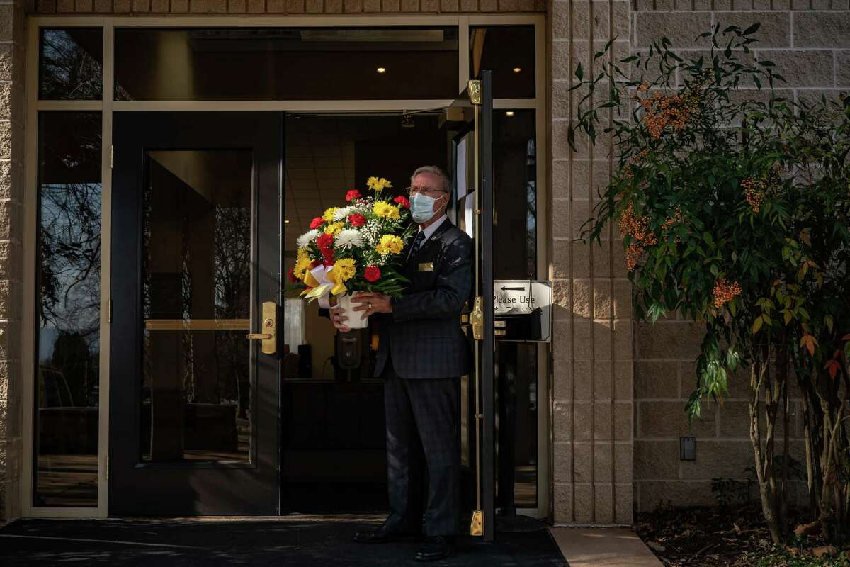 Ken Hammond, a funeral associate in Hagerstown, Md., holds flowers for the family of a man in his 50s who died of covid-19 in January 2021.