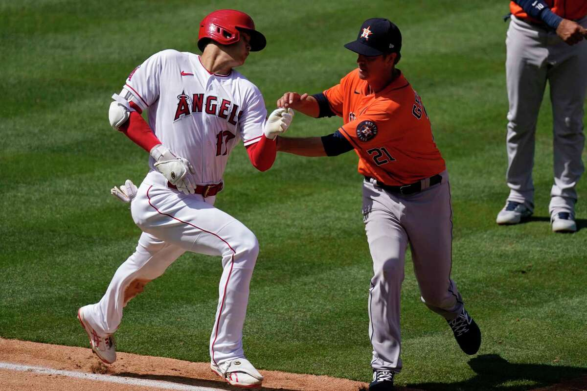 Los Angeles Angels' Shohei Ohtani, left, is tagged out as he runs to first by Houston Astros starting pitcher Zack Greinke during the fifth inning of a baseball game Tuesday, April 6, 2021, in Anaheim, Calif. (AP Photo/Mark J. Terrill)