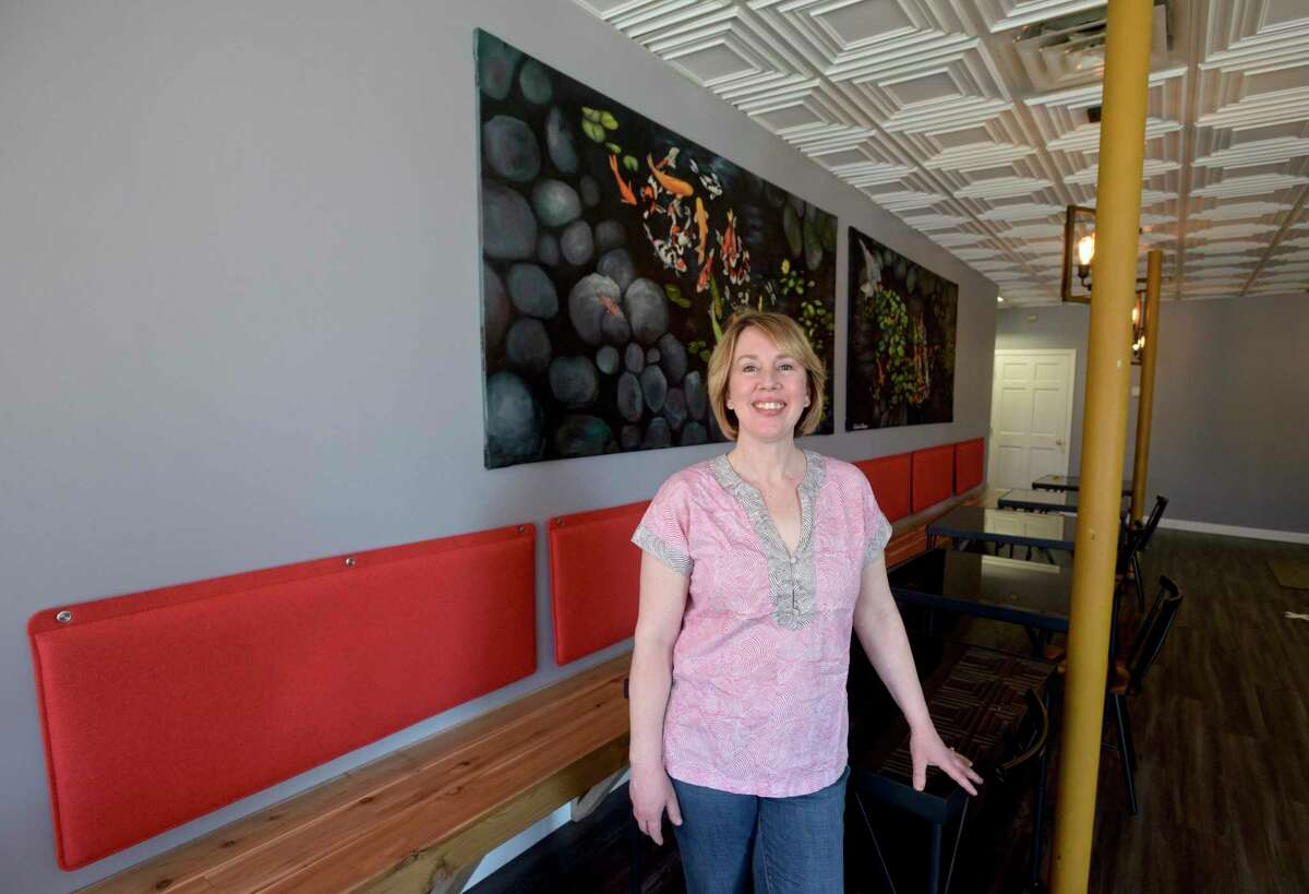 Anna Llamos owner of ItadakiMÀS Restaurant at 317 Main Street, in Danbury, Conn, April 2, 2021. The art work on the wall behind he was painted by her daughter Abigail Llanos.
