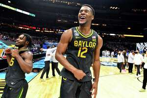 INDIANAPOLIS, INDIANA - APRIL 05:  Davion Mitchell #45and Jared Butler #12 of the Baylor Bears elebrate their win against the Gonzaga Bulldogs in the National Championship game of the 2021 NCAA Men's Basketball Tournament at Lucas Oil Stadium on April 05, 2021 in Indianapolis, Indiana.