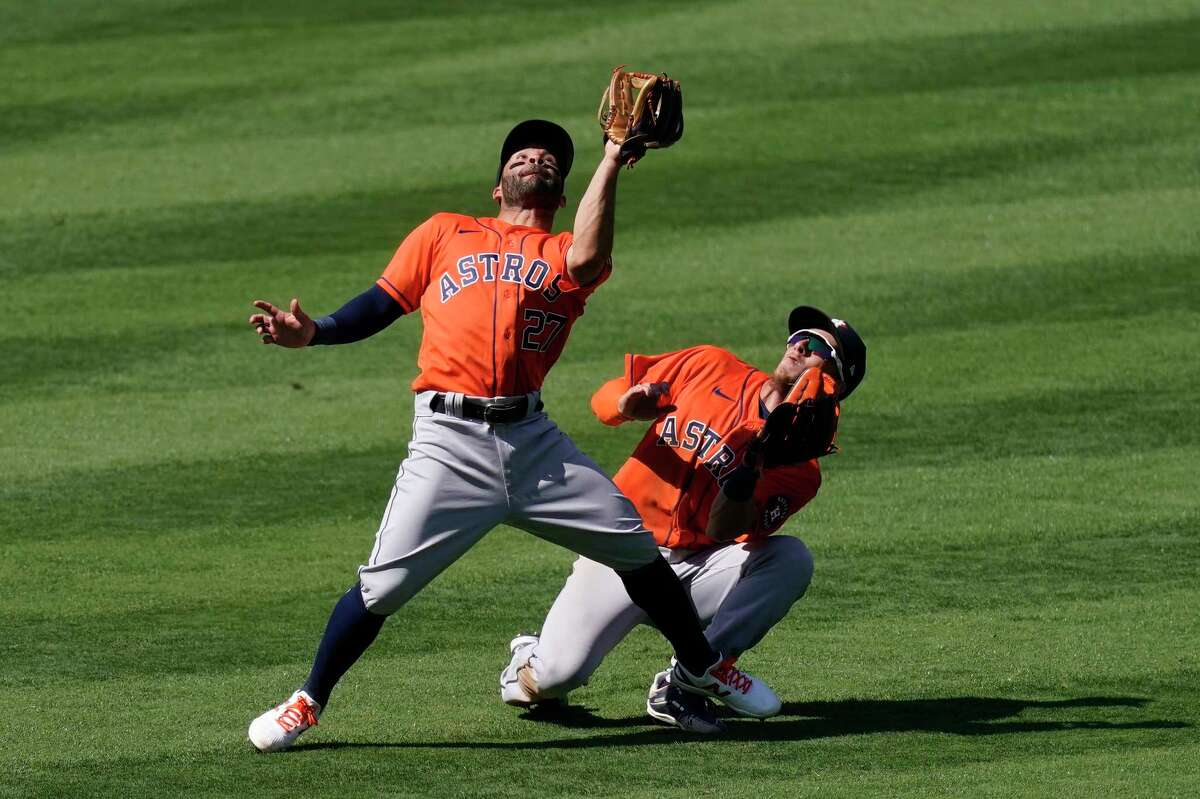 Houston Astros second baseman Jose Altuve, left, almost collides with center fielder Myles Straw as he makes a catch on a ball hit by Los Angeles Angels' Justin Upton during the seventh inning of a baseball game Tuesday, April 6, 2021, in Anaheim, Calif. (AP Photo/Mark J. Terrill)