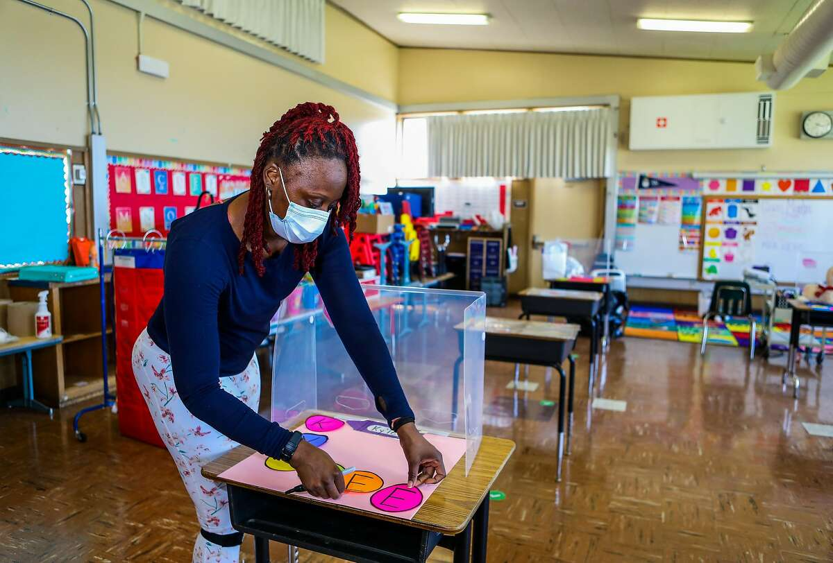 Shaione Simmons, who teaches transitional kindergarten and kindergarten, places a student's name on a desk as she preps her classroom at Madison Park Academy Primary on Thursday, March 25, 2021, in Oakland, Calif. The school is preparing to reopen on Tuesday.