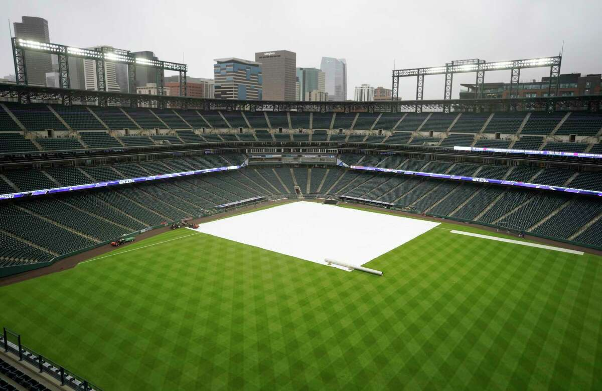 Grounds crew workers pull the tarpaulin as a light rain descends at Coors Field on Tuesday in Denver.