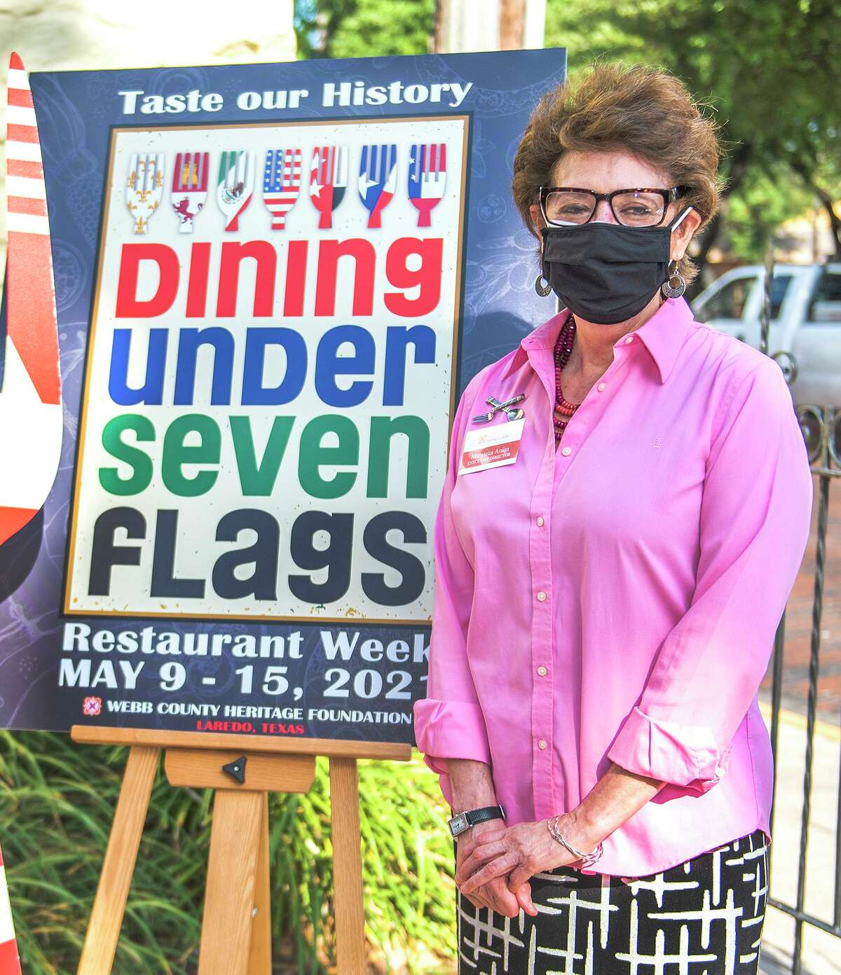 Webb County Heritage Foundation Executive Director Margarita Araiza poses for photos, Tuesday, Mar. 6, 2021, at La Posada Hotel's courtyard next to a sign promoting the foundation's restaurant week.