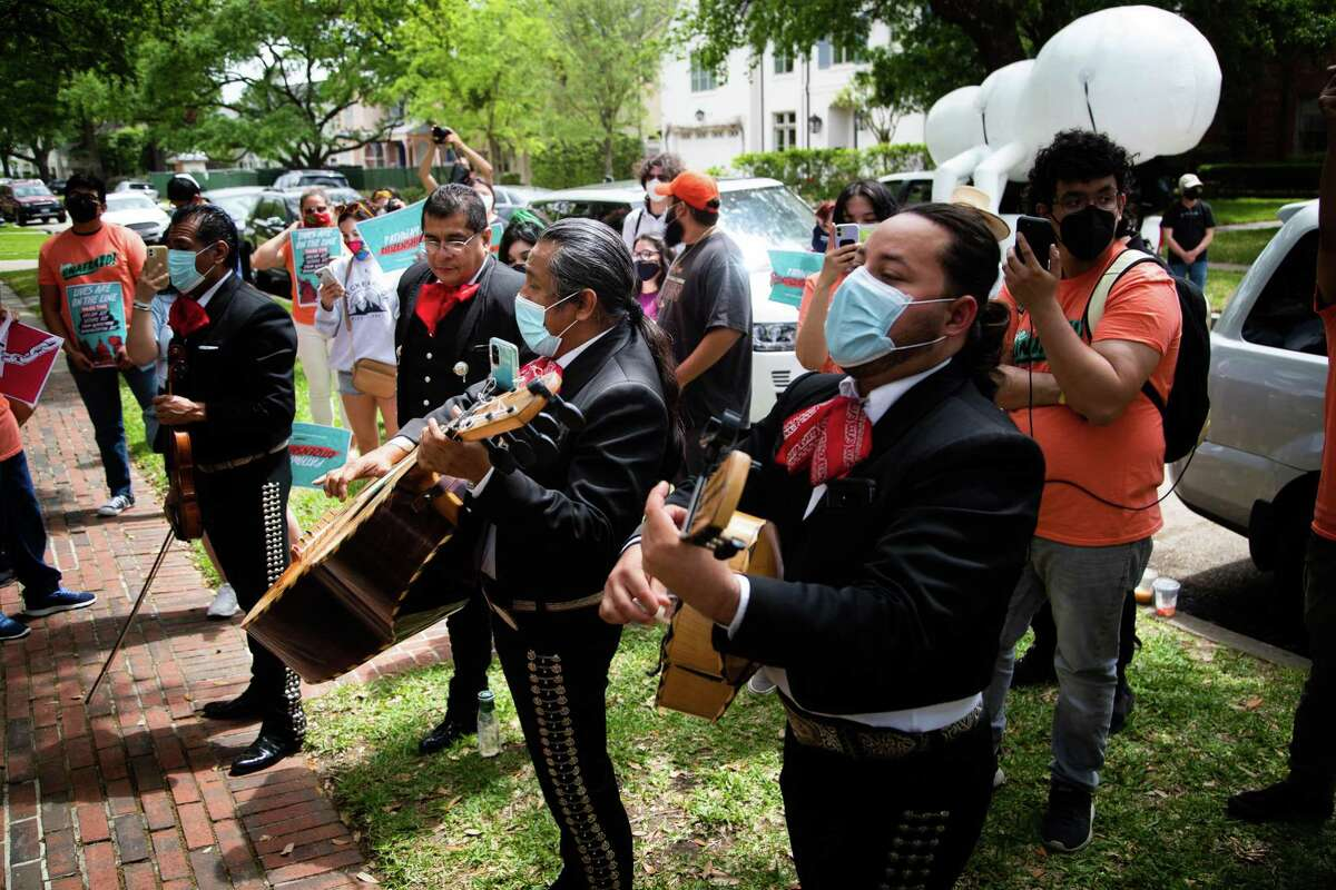 """Mariachi Calmecac performs in front of the residence of United States Senator Ted Cruz during a protest, Tuesday, April 6, 2021, in Houston. Different advocacy organizations and local members of the community attended the protest demanding Senators Ted Cruz and Senator John Cornyn to take immediate action to deliver a pathway to citizenship for immigrant youth, TPS holders and farm workers. The music group sang songs like """"La Cucaracha"""" and """"Rata de Dos Patas"""" during the protest."""