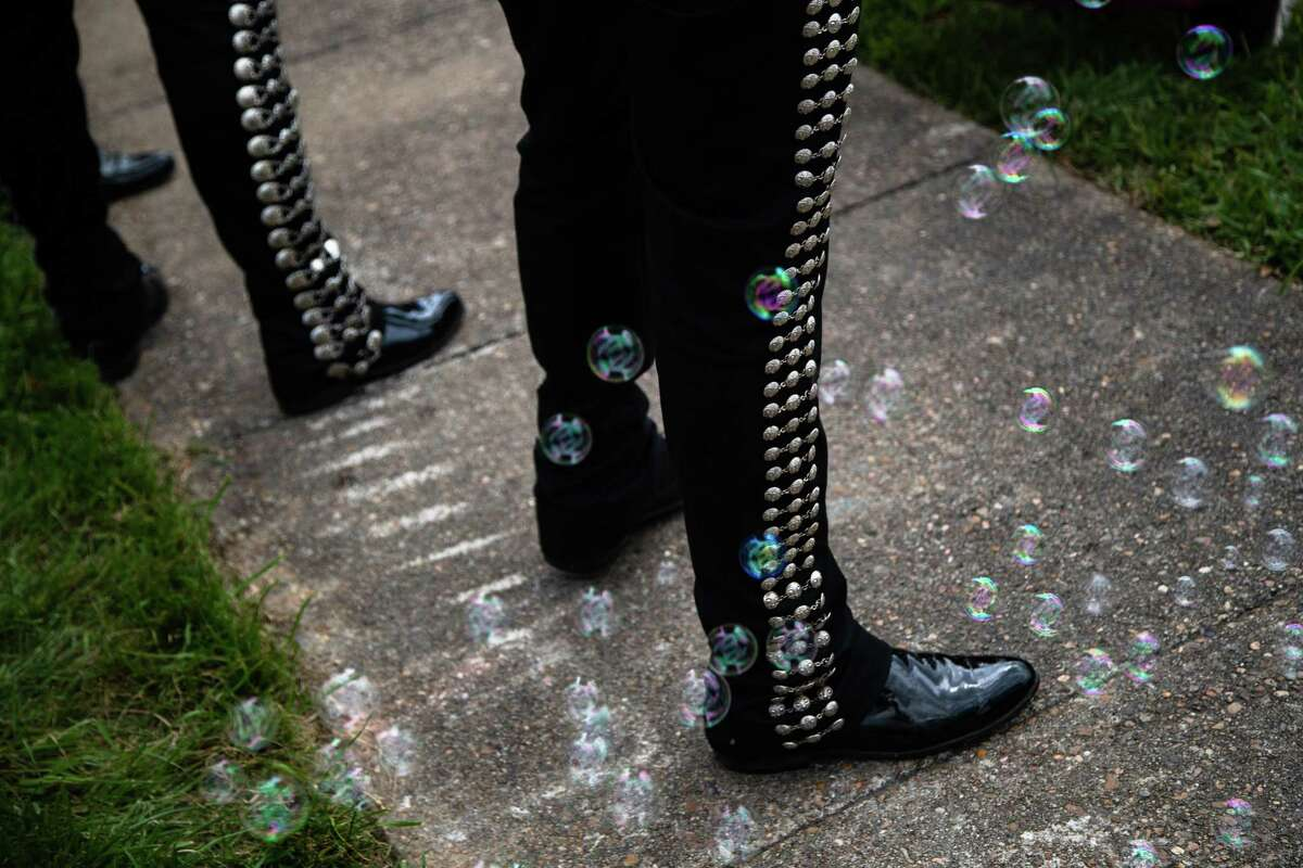 Mariachi pants surrounded by bubbles at a protest in front of United States Senator for Texas John Cornyn's offices, Tuesday, April 6, 2021, in Houston.