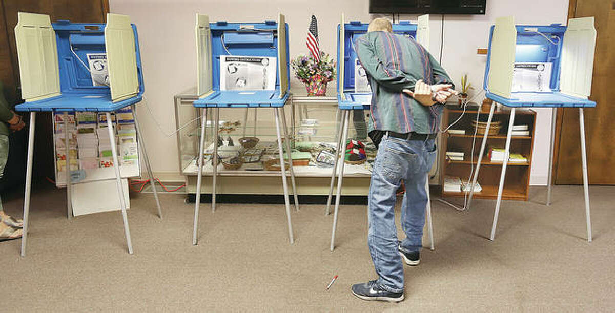 A voter in Alton Precinct 24 bends over Tuesday morning to read the voting instructions before filling out his ballot in the Messiah Lutheran Church, 920 Milton Road. Three Alton precincts vote in the church. Alton joined several other local municipalities who had mayoral races on the ballot Tuesday.
