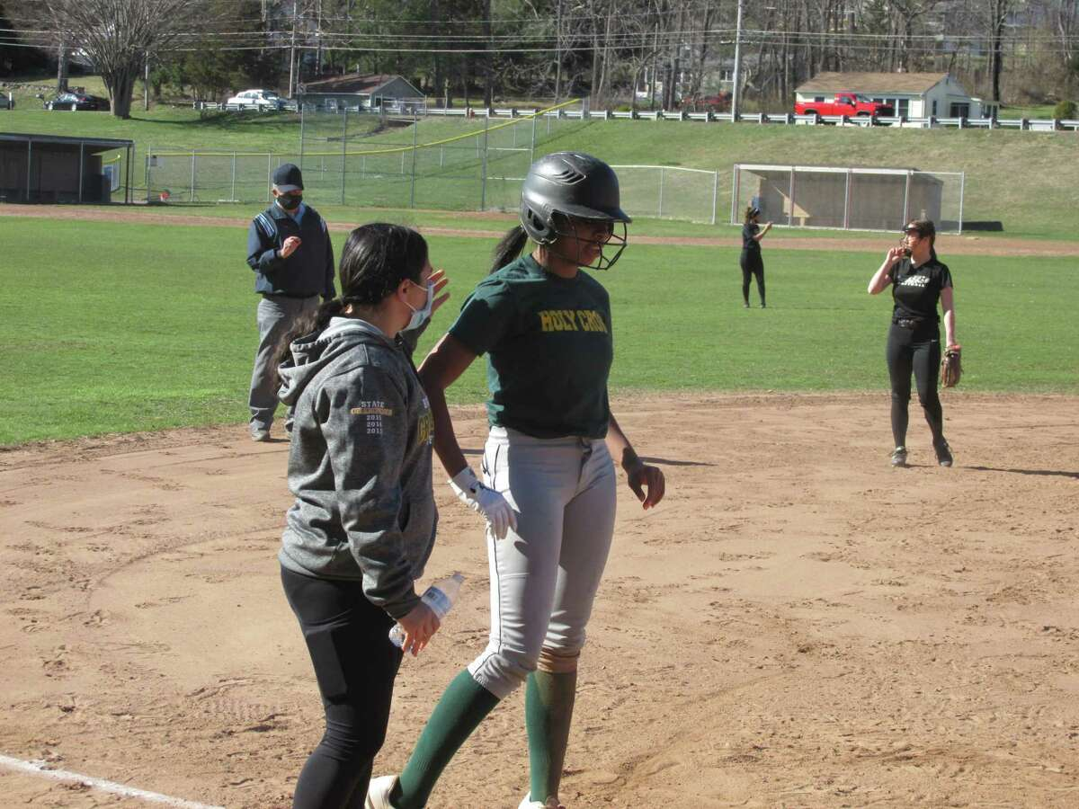 Holy Cross coach Meg Dwyer congratulates sophomore Tyra McCoy for an RBI triple in the early innings of a scrimmage at Thomaston High School Tuesday afternoon.