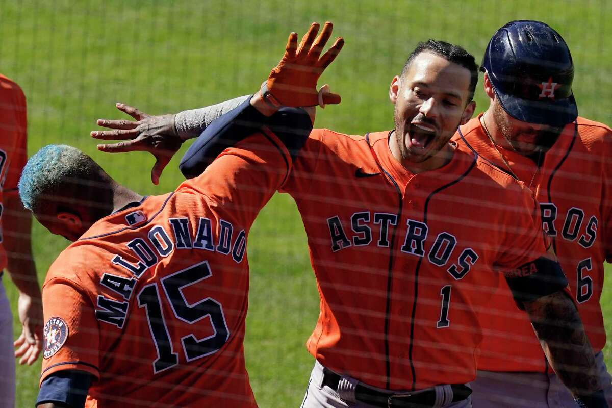 Houston Astros' Carlos Correa, center, celebrates with Martin Maldonado, left, after hitting a two-run home run as Chas McCormick walks behind during the ninth inning of a baseball game against the Los Angeles Angels Tuesday, April 6, 2021, in Anaheim, Calif. (AP Photo/Mark J. Terrill)