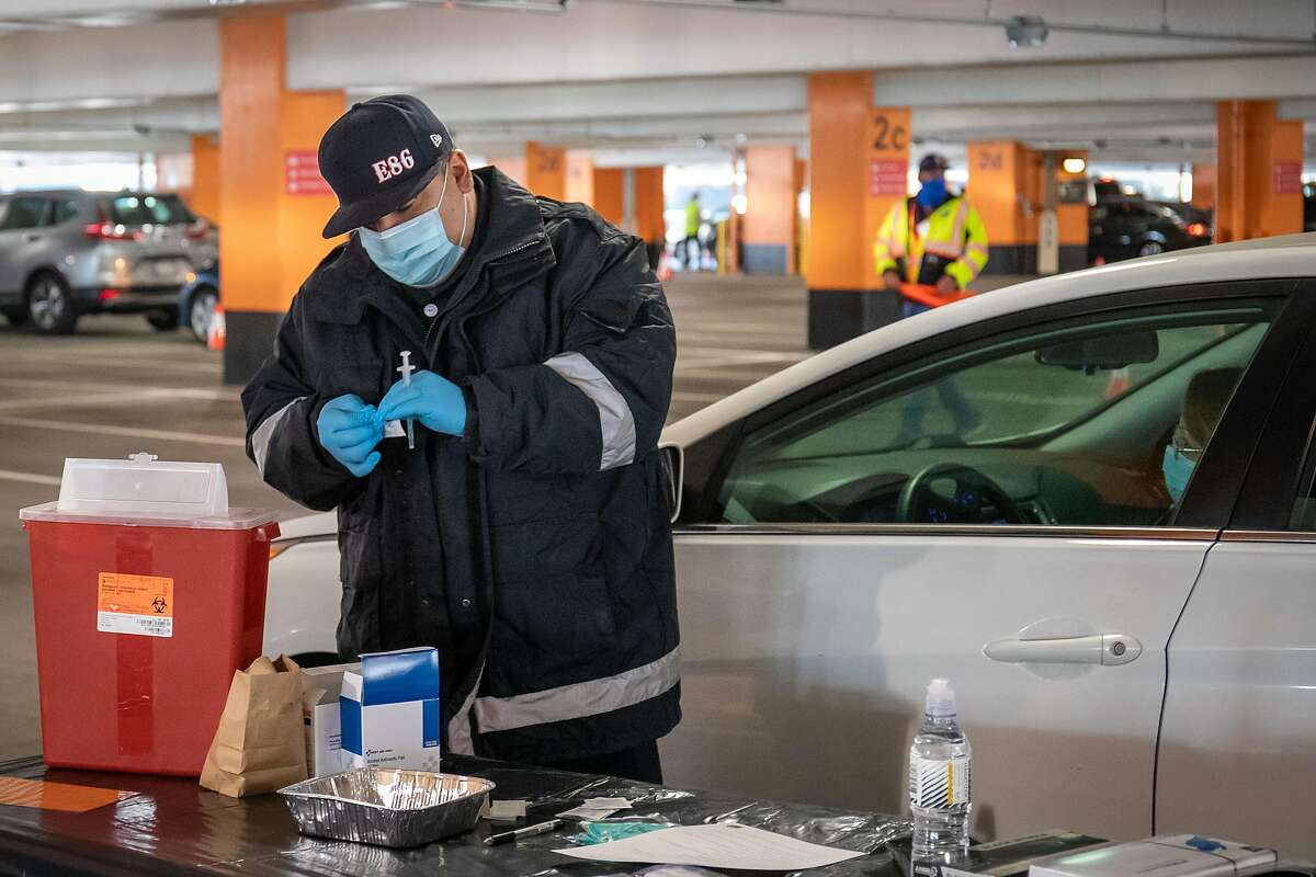 A volunteer helps with vaccinations in an SFO parking garage now being used as a vaccination center by San Mateo County.