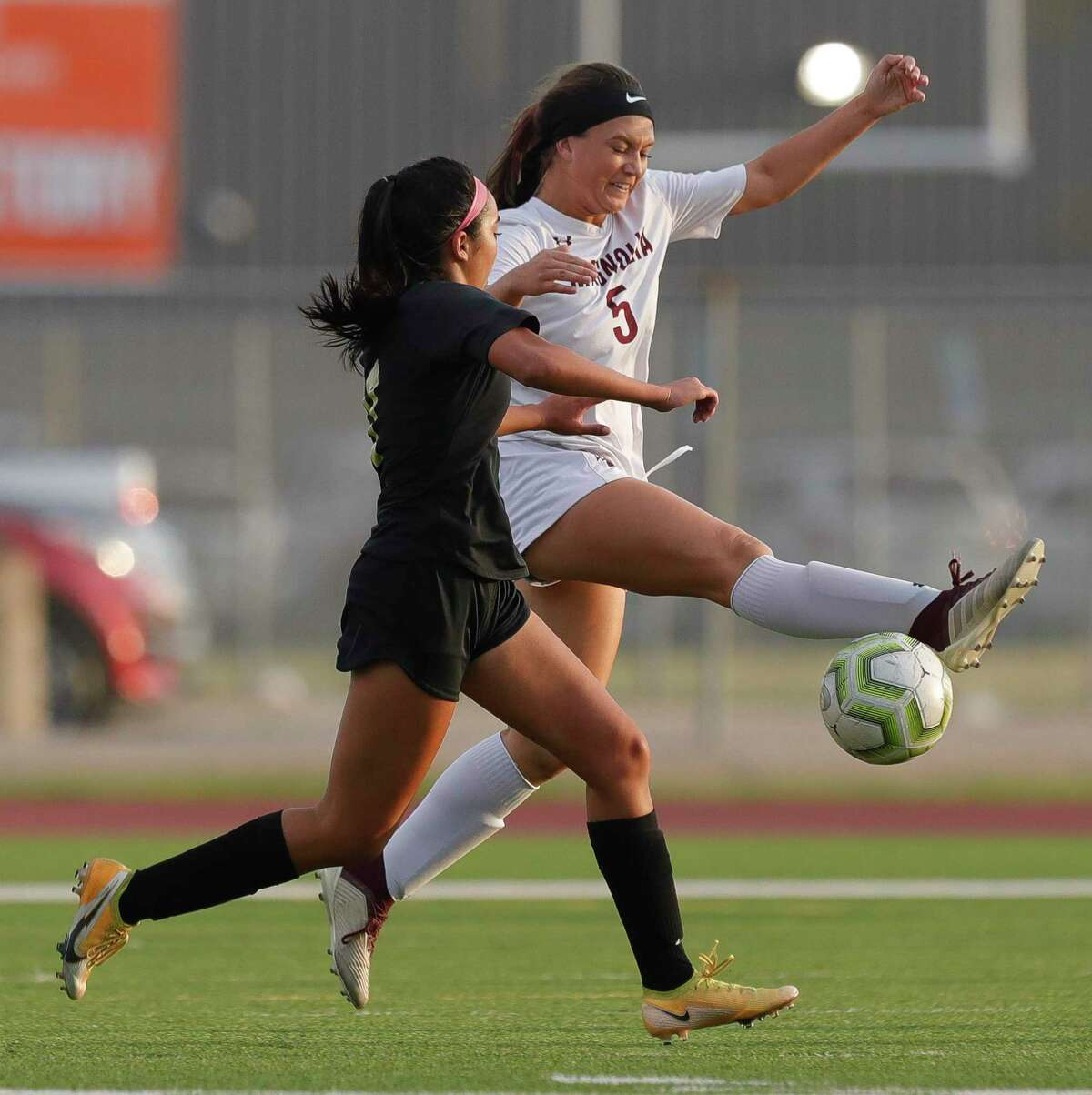 Magnolia's Avery Tindall (5) contests the ball against Foster's Abrie Morales (7) during the first period of a Region III-5A semifinal match at Cypress Falls High School, Tuesday, April 6, 2021, in Cypress.
