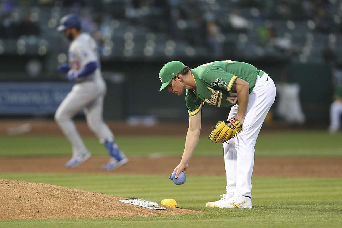 Oakland Athletics pitcher Chris Bassitt stands behind the mound as the Los Angeles Dodgers' Edwin Rios runs the bases after hitting a home run during the fourth inning of a baseball game in Oakland, Calif., Tuesday, April 6, 2021. (AP Photo/Jed Jacobsohn)