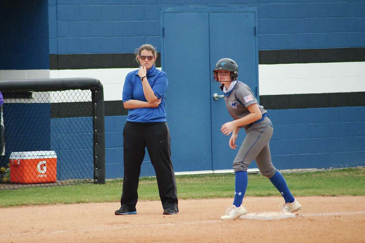 Friendswood's Baileigh Burtis, leading off third in front of Lady Mustang head coach Christa Yates, helped power FHS to an easy victory Tuesday night over Goose Creek Memorial.