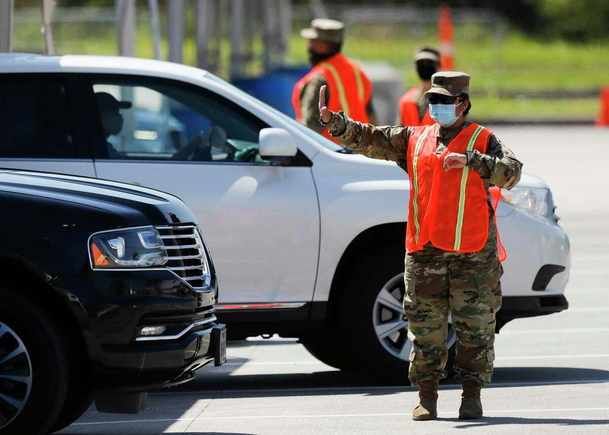 A solider with the National Guard directs pacients after recieving their COVID-19 vaccine at Montgomery County's mass vaccination site at The Woodlands Bank Stadium, Thursday, April 1 2021, in Shenandoah.