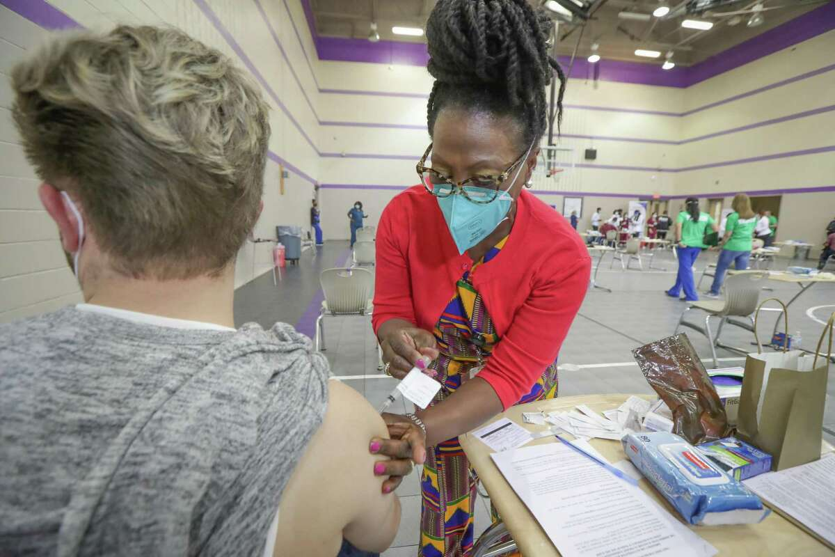 Monica Lewis, HISD RN, gives Alejandro Regules a COVID-19 vaccine during a neighborhood outreach vaccination site at Wheatley High School Friday, April 2, 2021, in Houston.