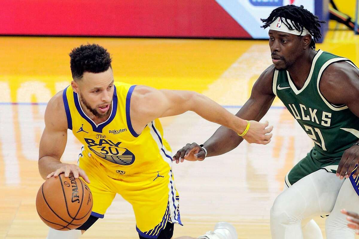 Stephen Curry (left) drives to the basket defended by Jrue Holiday during a Warriors game at Chase Center this week.