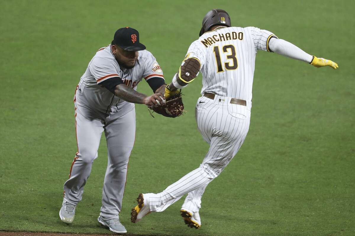 San Francisco Giants relief pitcher Reyes Moronta tags out San Diego Padres' Manny Machado during the sixth inning of a baseball game Tuesday, April 6, 2021, in San Diego. (AP Photo/Derrick Tuskan)