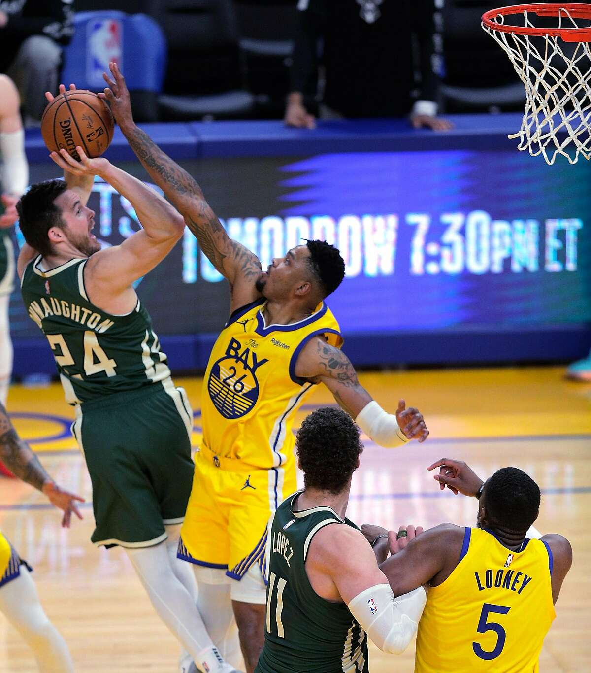 Kent Bazemore (26) blocks Pat Connaughton's (24) final shot in the second half as the Golden State Warriors defeated the Milwaukee Bucks 122-121 at Chase Center in San Francisco Calif., on Tuesday, April 6, 2021.