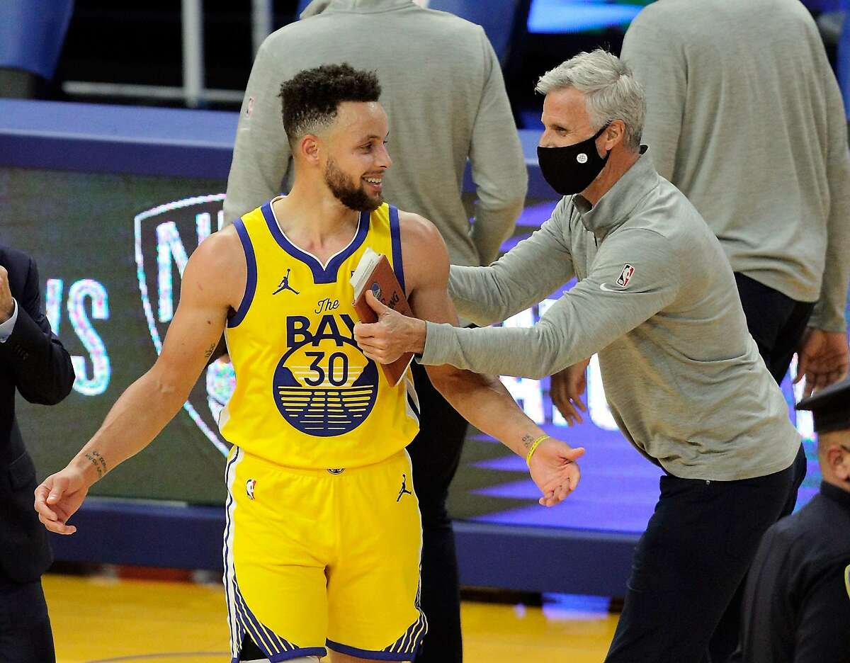 Stephen Curry (30) gets a hug from coach Bruce Fraser after the Golden State Warriors defeated the Milwaukee Bucks 122-121 at Chase Center in San Francisco Calif., on Tuesday, April 6, 2021.