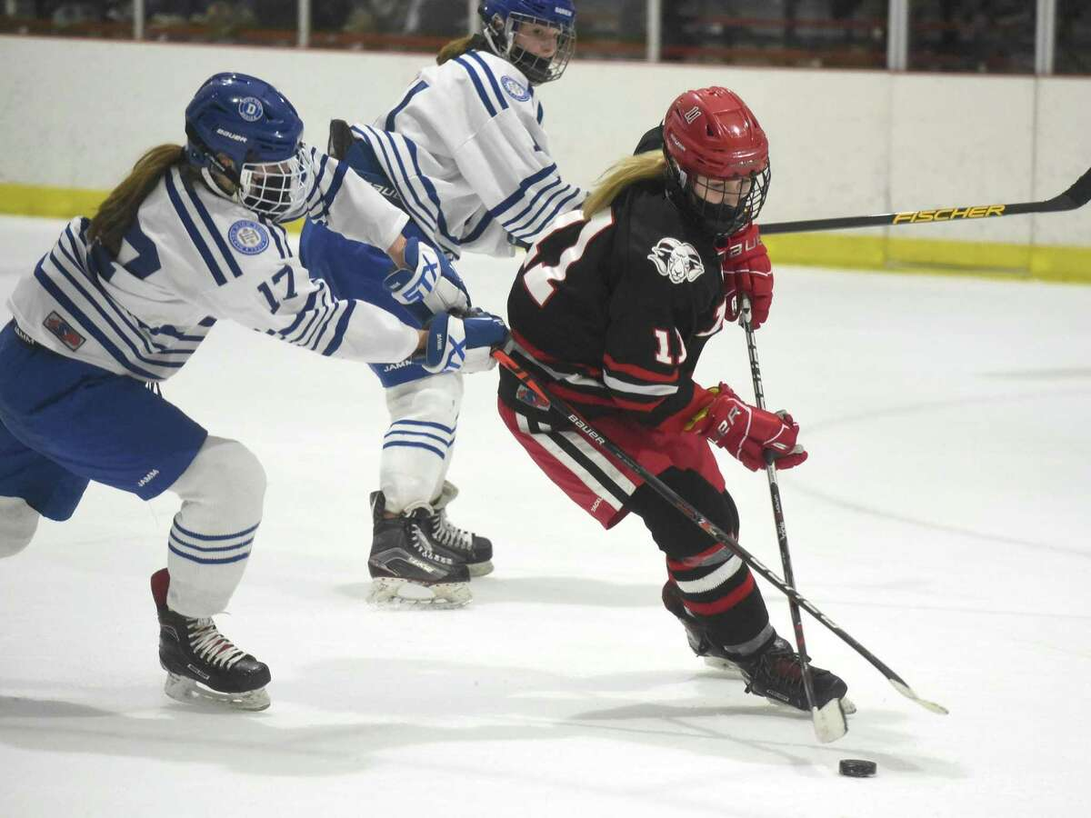 New Canaan's Kelly Benson (11) skates to the net with Darien's Morgan Massey (17) in pursuit during the FCIAC girls ice hockey final at the Darien Ice House on Saturday, March 20, 2021.