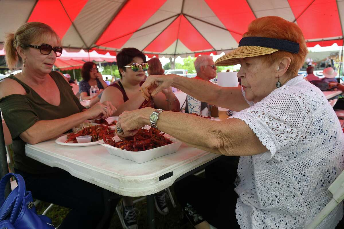 Alisa Gonzalez, of Hockley, from left, her daughter Maggie, 23, a student in the EMT program at Lone Star College - Tomball, and her mom Sandra Lamarche, of Houston, dine on bolied crawfish from the French Quarter Cajun Seafood Restaurant (in Cy-Fair) booth during the Tomball 7th Annual Rails & Tails Mudbug Festival at the Tomball Depot on May 5, 2018. (Photo by Jerry Baker/Freelance)