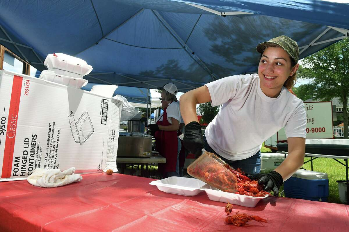 Brooke Fotech, 22, serves up an order of crawfish at the French Quarter Cajun Seafood Restaurant (in Cy-Fair) booth during the Tomball 7th Annual Rails & Tails Mudbug Festival at the Tomball Depot on May 5, 2018. (Photo by Jerry Baker/Freelance)