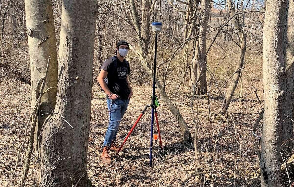 Wesleyan University student Xavier Lopez surveys the location of a vegetation plot using a high-precision GPS in Middletown.