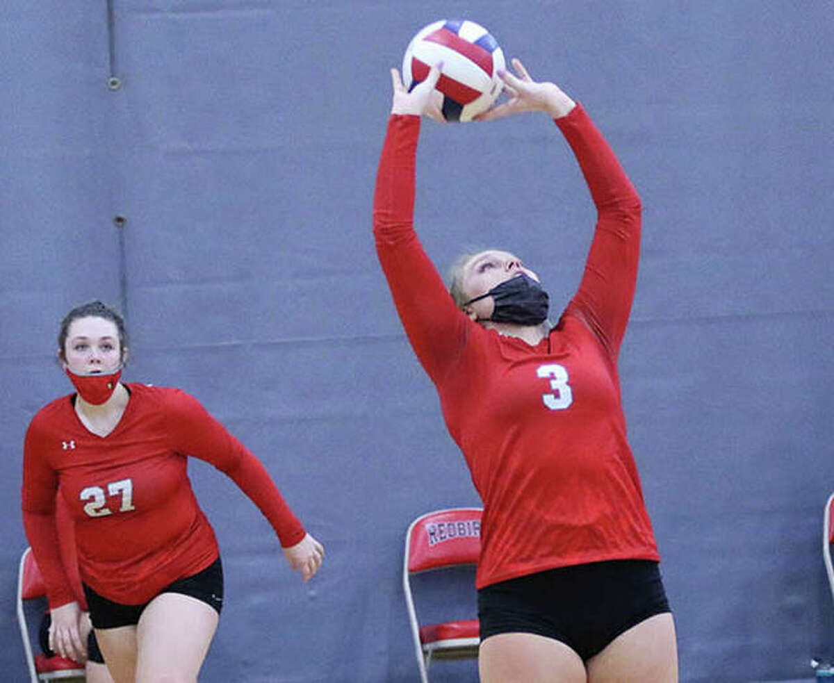 Alton's Taylor Freer (3), shown setting while teammate Olivia Ducey heads to the net in a match earlier this season, had three assists in the Redbirds' loss to O'Fallon on Tuesday in a first-round match of the SWC Tourney in O'Fallon.
