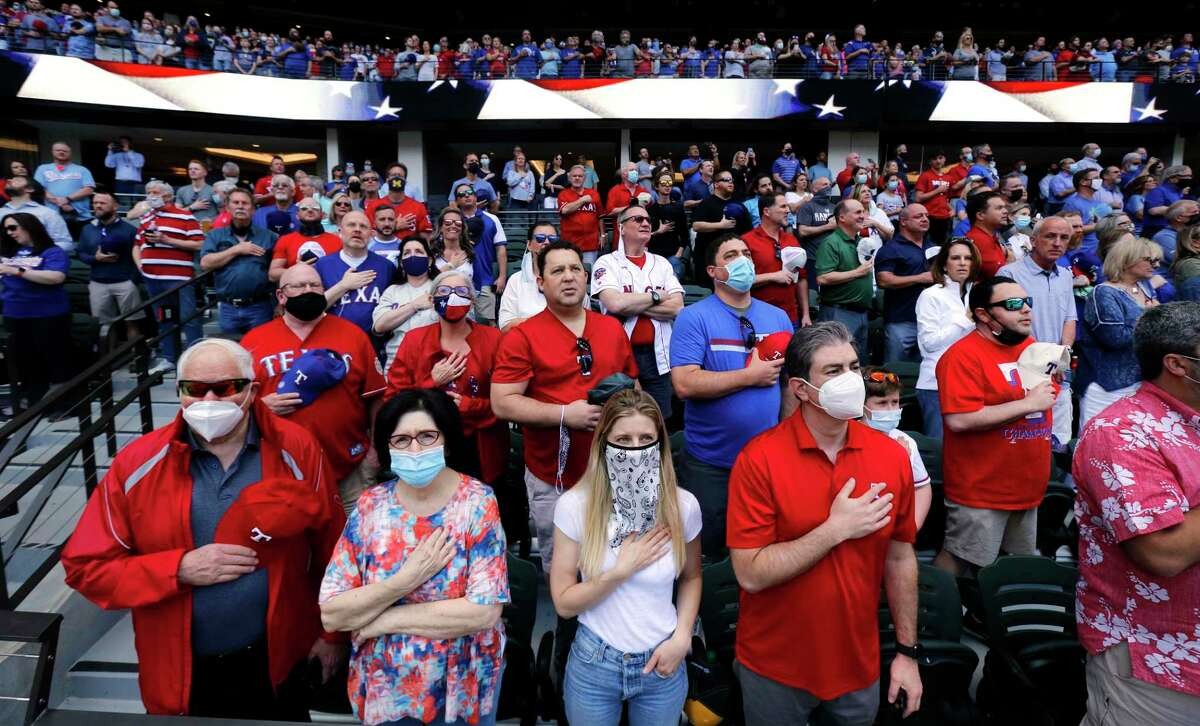 Texas Rangers fans (from left) Fred Aurbach, his girlfriend Leslie Lehman, his daughter-in-law Melissa Aurbach and son Wilson Aurbach and the rest of the nearly sold-out Opening Day crowd stand for the national anthem at Globe Life Field in Arlington, Texas on Monday, April 5, 2021. The Rangers were facing the Toronto Blue Jays in the home opener.