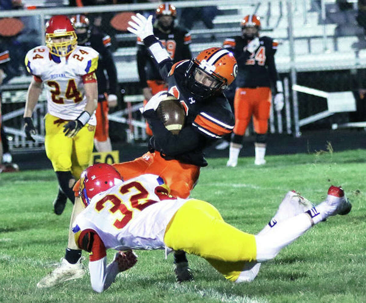 Gillespie's Trenton Bertolis is tackled by Roxana's Rolen Ross (32) in the first half of a South Central Conference football game Friday night at Don Dobrino Field in Gillespie.