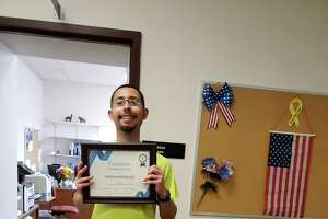 Erik Rodriguez, a member of Cromwell's building maintenance department, with a certificate of appreciation presented to him during a farewell ceremony in Town Hall last week.