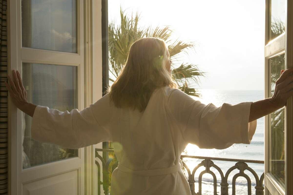 Woman opens window over sea, in bath robe