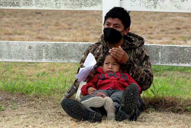 A migrant man sits with his young son while waiting to be processed by Border Patrol in La Joya. Photo: Jessica Phelps / ©2021 San Antonio Express-News