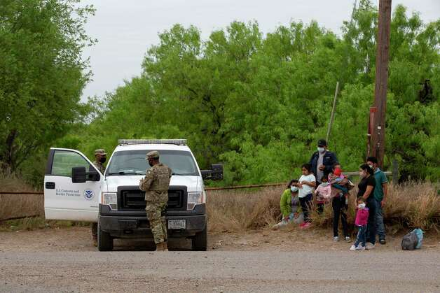 Two families in La Joya wait with Border Patrol to be taken to a larger group of migrants before being taken on a bus to be processed. Photo: Jessica Phelps / ©2021 San Antonio Express-News