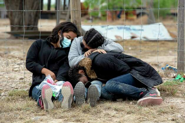 Three teenage girls, one from El Salvador aged 17, and from Honduras ages 14 and 16 all huddle together in La Joya, exhausted from their journey, as they wait for Border Patrol to process them. Photo: Jessica Phelps / ©2021 San Antonio Express-News
