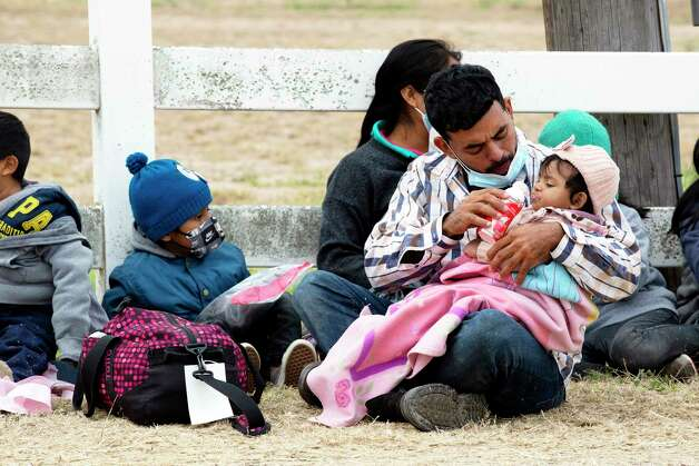 A migrant man feeds his young child yogurt while waiting to be process by Border Patrol in La Joya. He was among a group of 62 people, all families with young children and 5 unaccompanied minors. Photo: Jessica Phelps / ©2021 San Antonio Express-News