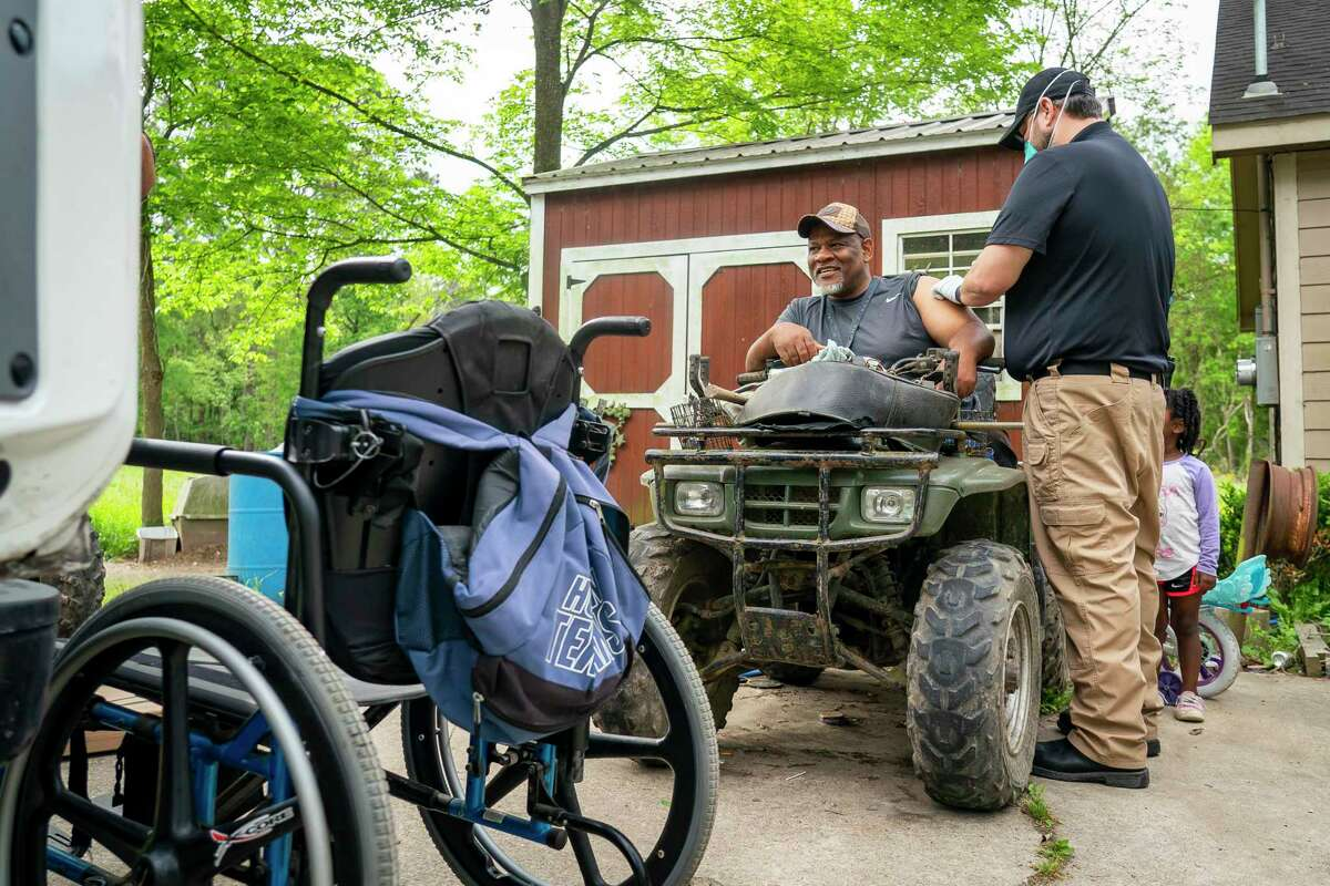 Chambers County paramedic Danny Burke administers the first dose of the Moderna COVID-19 vaccine to Grady Carrington outside of Carrington's home, Tuesday, April 6, 2021, in Hankamer, TX. Carrington, who was sitting on an ATV while his wheelchair was being serviced by a mobile service truck when Burke arrived, decided to get the vaccine when his doctor told him he needed to get it. After failing to sign up online, Carrington called the county and they told him they had a mobile service that could come to him which he said was good because it meant he did not have to find a ride. The Chambers County ambulance service has been administering vaccines to people in their homes.