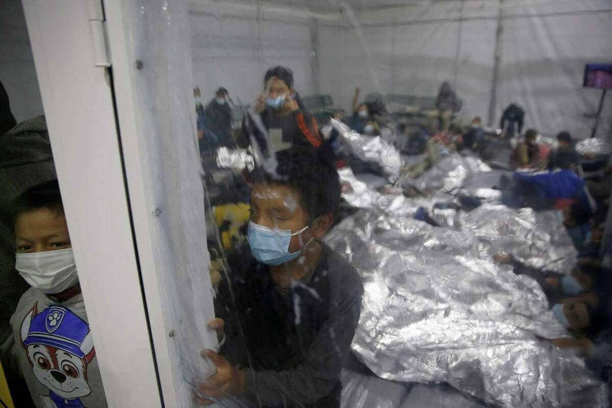 Young children look out from inside a pod at the Donna Department of Homeland Security holding facility, the main detention center for unaccompanied children in the Rio Grande Valley run by the Customs and Border Patrol (CBP), in Donna, Texas on March 30, 2021. - The children are housed by the hundreds in eight pods that are about 3,200 square feet in size. Many of the pods had more than 500 children in them. The Biden administration on Tuesday for the first time allowed journalists inside its main detention facility at the border for migrant children, revealing a severely overcrowded tent structure where more than 4,000 kids and families were crammed into pods and the youngest kept in a large play pen with mats on the floor for sleeping. (Photo by Dario Lopez-Mills / POOL / AFP) (Photo by DARIO LOPEZ-MILLS/POOL/AFP via Getty Images)
