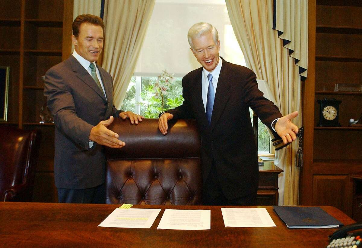 Gov.-elect Arnold Schwarzenegger (left) jokes with outgoing Gov. Gray Davis in October 2003 after voters recalled Davis.
