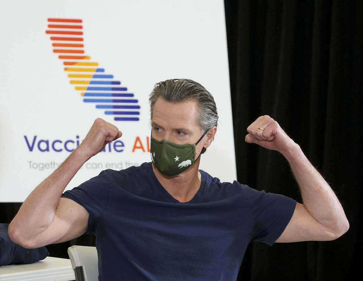 California Gov. Gavin Newsom reacts after being inoculated by Dr. Mark Ghaly, secretary of California Health and Human Services at the Baldwin Hills Crenshaw Plaza in Los Angeles Thursday, April 1, 2021.