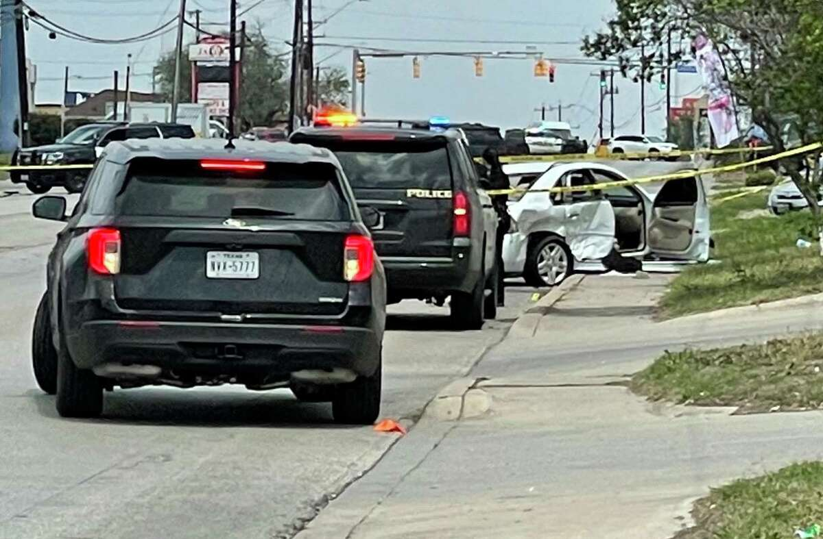 A damaged car sits on the sidewalk surrounded by police cars Wednesday, April 7, 2021, in the 12400 block of Nacogdoches after a shootout between people in two moving vehicles.