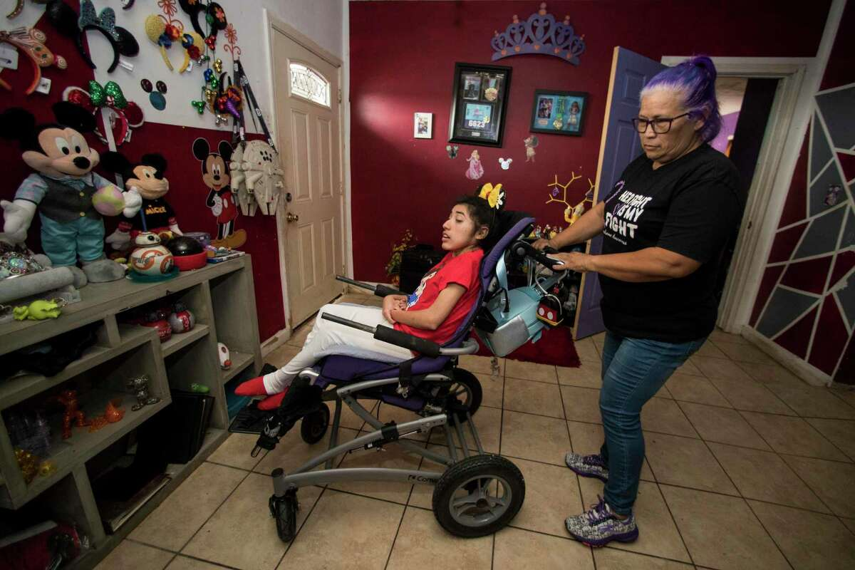 Olivia Esparza wheels her daughter, Diana Santana, 21, into a Disney themed room at their home Saturday, April 3, 2021 in Houston.
