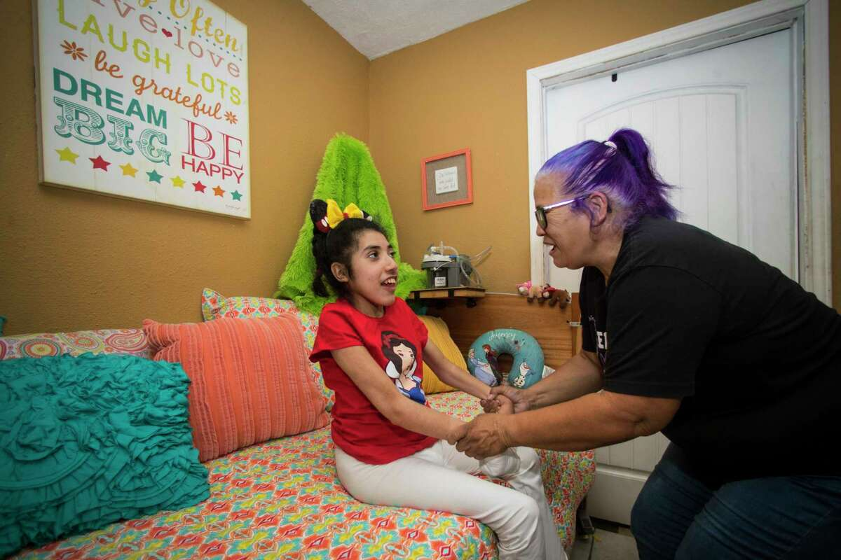 Olivia Esparza helps her daughter, Diana Santana, 21, sit up on a day bed in her room Saturday, April 3, 2021 in Houston.