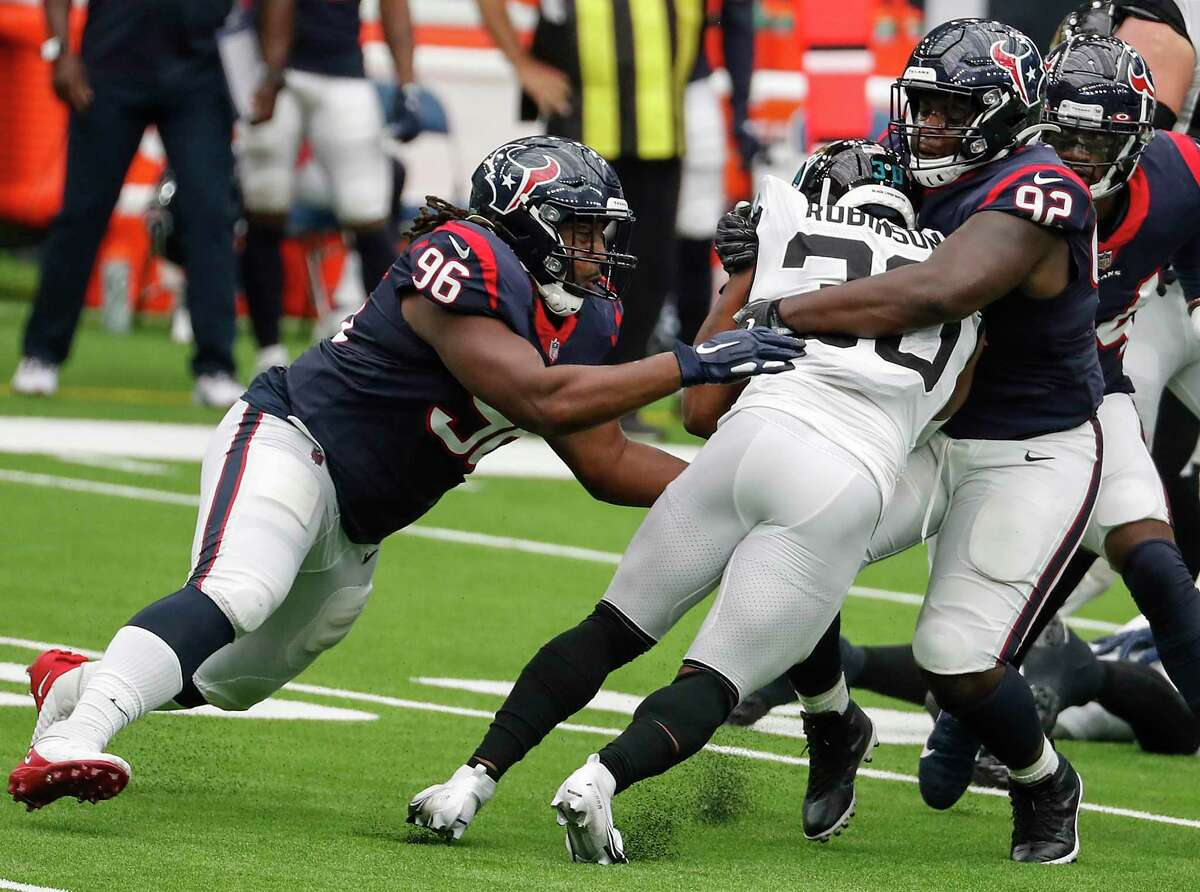 Houston Texans defensive end P.J. Hall (96) and nose tackle Brandon Dunn (92) tackle Jacksonville Jaguars running back James Robinson (30) during the first half of an NFL football game at NRG Stadium on Sunday, Oct. 11, 2020, in Houston.