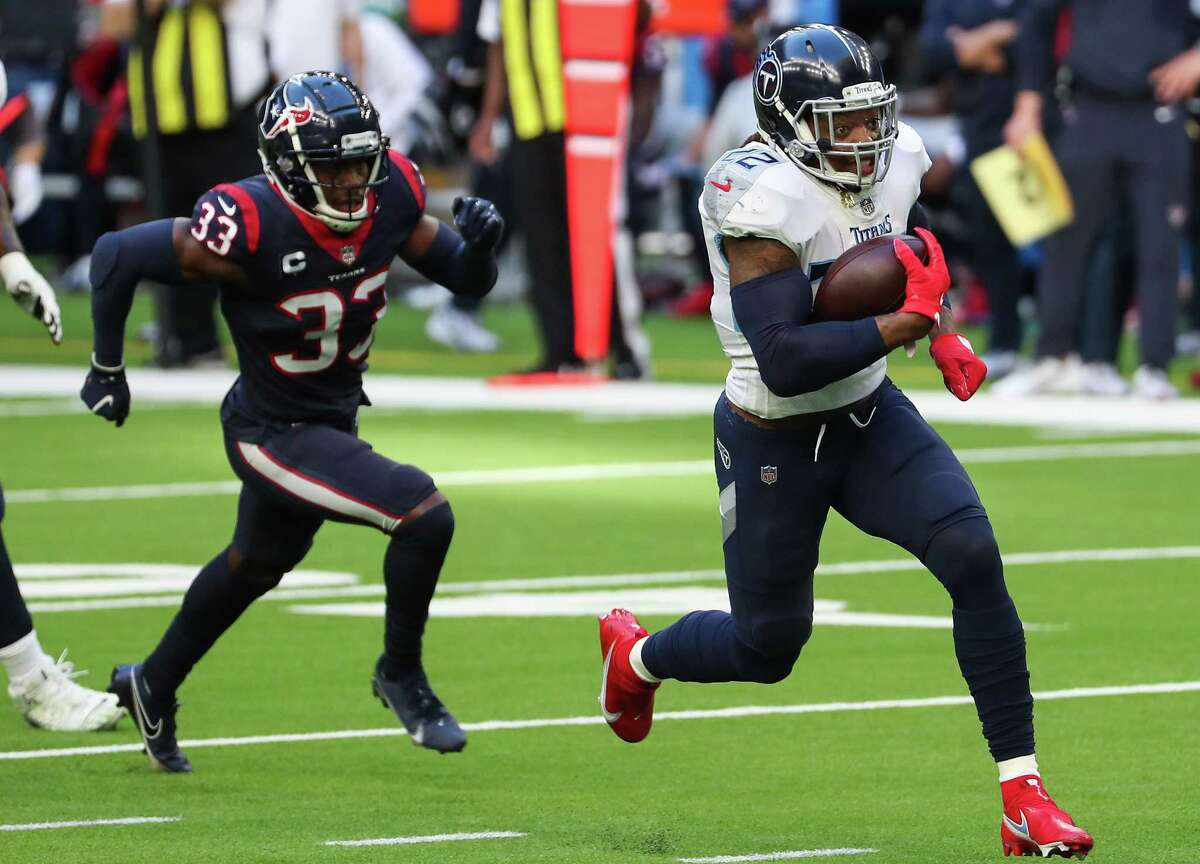 Tennessee Titans running back Derrick Henry (22) runs past Houston Texans safety A.J. Moore (33) on his way to a 52-yard touchdown run during the second quarter of an NFL football game at NRG Stadium on Sunday, Jan. 3, 2021, in Houston.