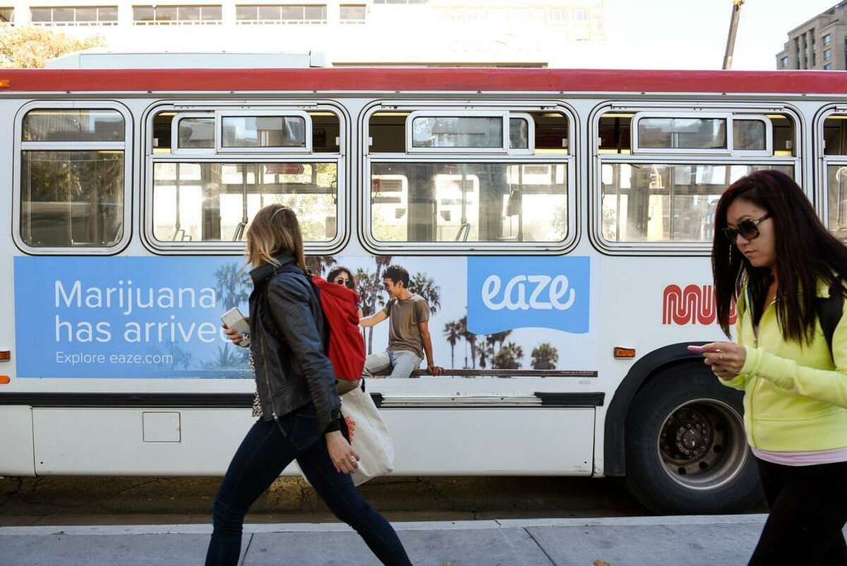 Pedestrians walk past an advertisement on the side of a MUNI bus for marijuana delivery service Eaze in downtown San Francisco, CA, on Friday November 17, 2017.