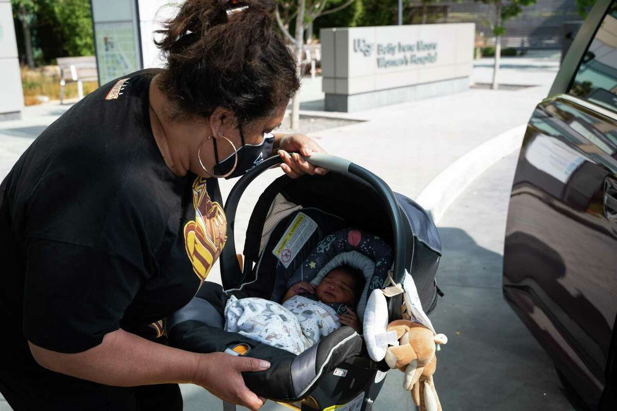 Epenesa Taylor-Togiai admires her newborn granddaughter Oshún Rae'Lynn-Ku'ulpo Togiai-Stevé after she is discharged from UCSF Hospital in San Francisco, Calif., on Saturday, August 1, 2020.
