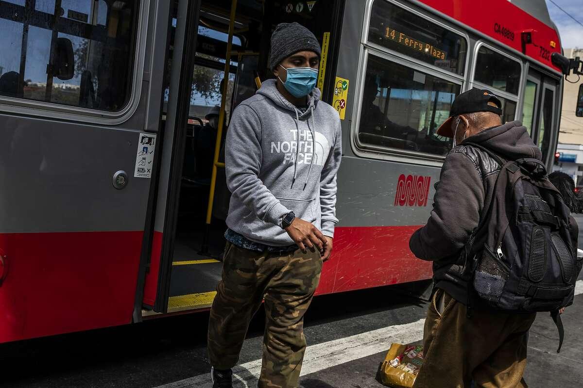 Masked pedestrians walk along Mission Street in the Excelsior district in San Francisco on April 7, 2021.