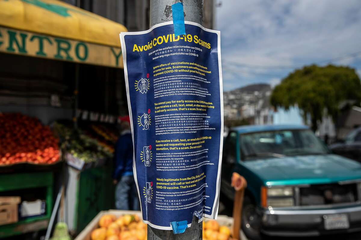A poster warning against COVID-19 scams is seen posted on a pole in the Excelsior district of San Francisco, California Wednesday April 7, 2021.